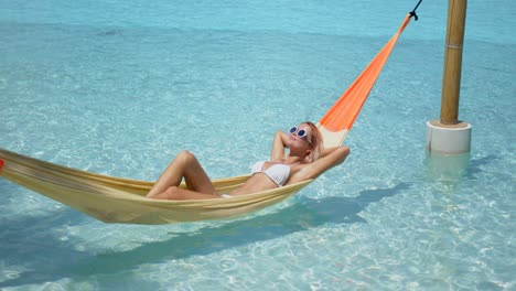 Relaxed-woman-lying-on-hammock-over-pool
