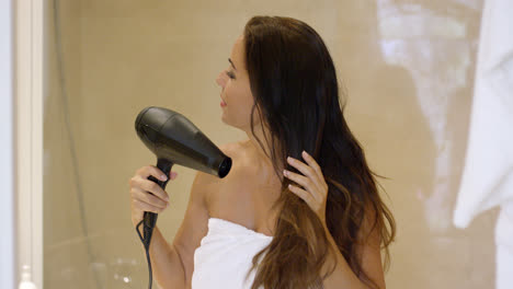Young-woman-drying-her-long-dark-brown-hair