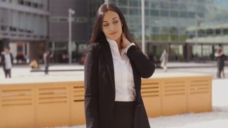 Smart-young-businesswoman-rubbing-her-neck
