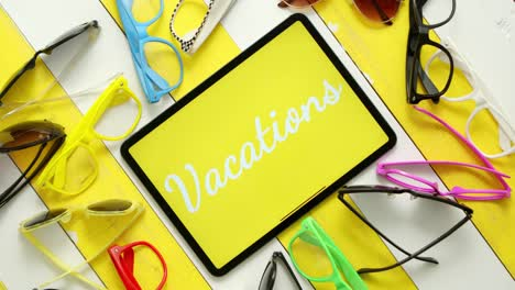 Various-style-shape-and-colour-sunglasses-Tablet-in-the-middle-with-text-VACATIONS-