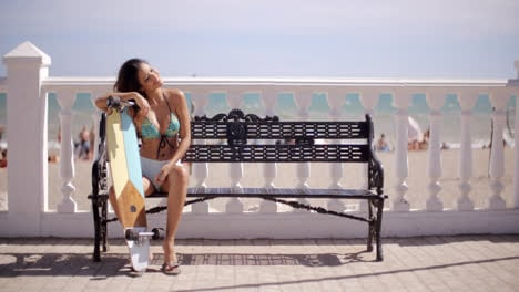 Sexy-young-woman-resting-on-her-skateboard