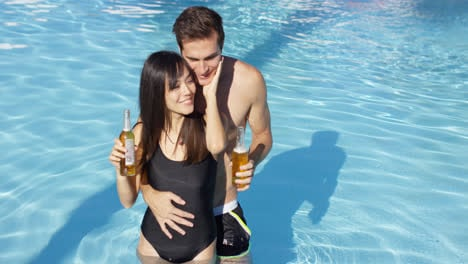 Couple-in-swimming-pool-hold-frothy-drinks