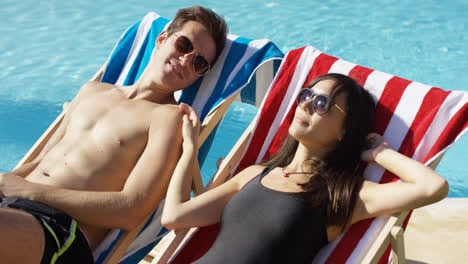 Young-couple-relaxing-at-a-resort-swimming-pool