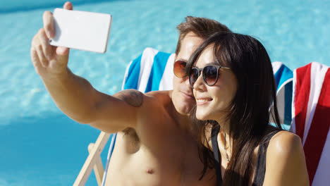Man-taking-picture-of-himself-with-wife-at-pool