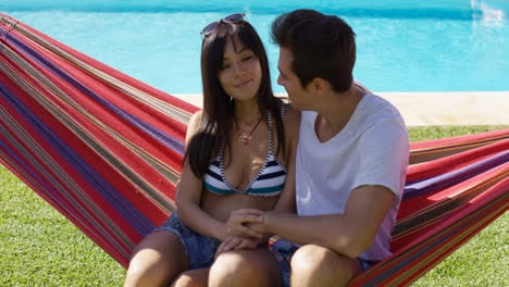 Loving-young-couple-sitting-on-a-hammock