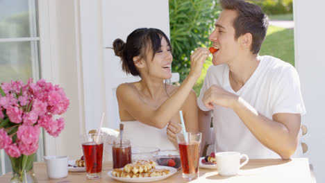 Couple-feeding-each-other-at-breakfast