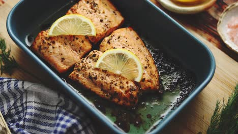 Roasted-salmon-in-heat-proof-dish-With-aromatic-dill-lemon-salt-and-pepper-on-sides-