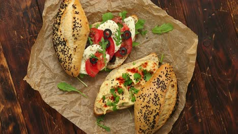 Two-delicious-sandwiches-with-hummus-tomato-mozarella-cheese-herbs-and-olives