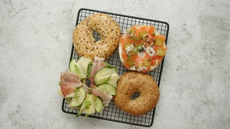 Two-Delicious-Bagel-sandwiches-with-ham-and-cheese-smoked-salmon-and-various-herbs-and-vegetables