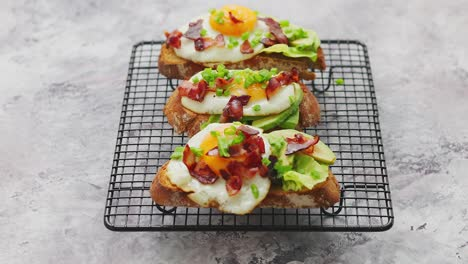 Tasty-delicious-homemade-toasts-with-fried-egg-bacon-avocado-lettuce-and-chive-Served-on-grill