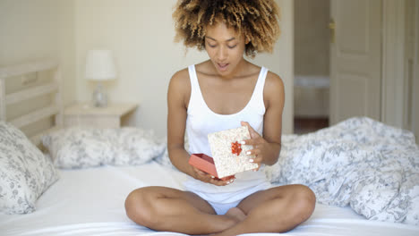 Happy-Young-Woman-Open-Gift-Box-In-Bedroom