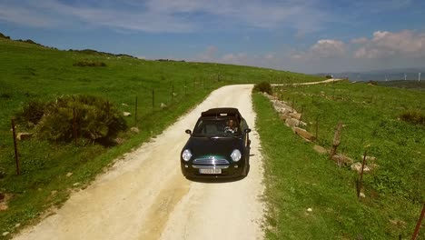 Young-woman-driving-a-cabriolet-on-a-dirt-road