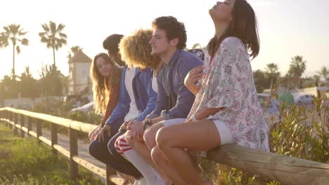 Young-People-Sitting-On-Wooden-Fence-