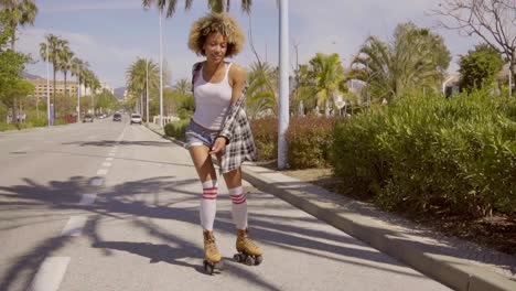 Young-black-woman-roller-skating-along-the-road