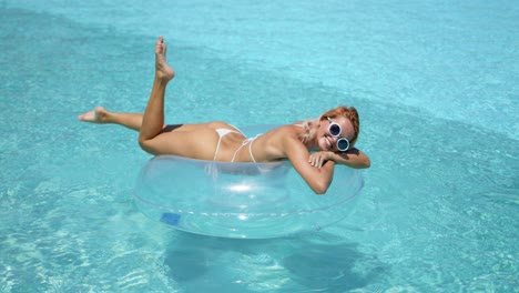 Woman-on-rubber-ring-sunbathing-in-swimming-pool
