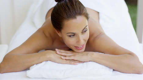 Woman-smiles-and-relaxes-on-massage-table