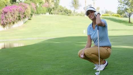 Smiling-female-golfer-with-brown-hair-crouches