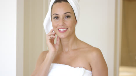Woman-wrapped-in-towel-smiles-at-camera