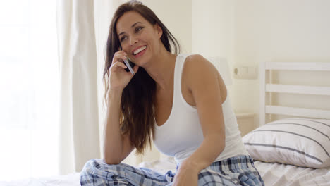 Young-woman-sitting-on-a-bed-chatting-on-a-mobile