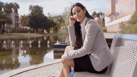 Gorgeous-business-woman-sitting-on-bench