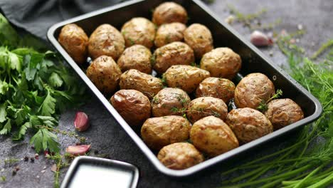 Tasty-fresh-homemade-baked-potatoes-served-on-a-metal-tray-With-various-herbs-butter-garlic-salt