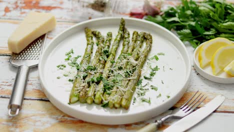 Delicious-roasted-asparagus-served-on-white-ceramic-plate-With-parmesan-cheese-parsley-and-lemon-