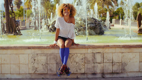 Happy-Sexy-Girl-Sitting-on-Fountains-Wall