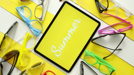 Various-style-shape-and-colour-sunglasses-Tablet-in-the-middle-with-text-SUMMER-