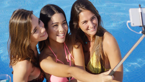 Three-young-women-taking-a-selfie-in-the-pool