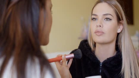 Woman-Putting-Make-up-to-her-Pretty-Friend