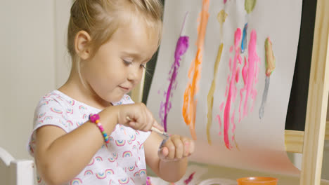 Little-girl-applying-paint-to-the-back-of-her-hand
