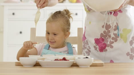 Laughing-girl-with-muffin-cups-and-parent-in-apron