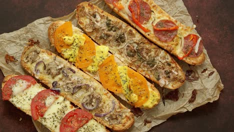 Composition-of-hot-tasty-baked-sandwiches-with-various-toppings-Cheese-tuna-mozarella-spices