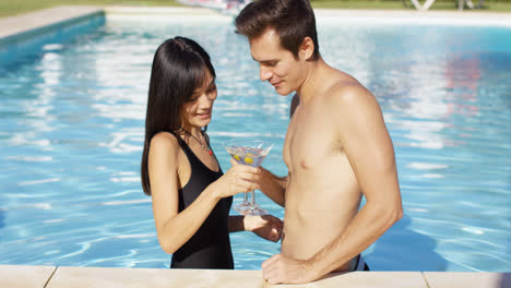 Cute-mixed-couple-holding-martini-glasses-in-pool