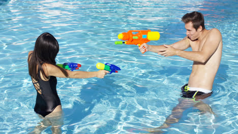 Happy-couple-shooting-off-water-guns-in-pool