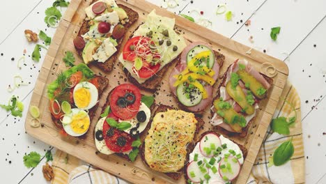 Colorful-different-kinds-sandwiches-served-on-wooden-chopping-board-Vegetable-toppings