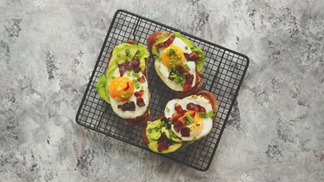 Breakfast-concept-Tasty-delicious-homemade-toasts-with-fried-egg-bacon-avocado-lettuce-and-chive