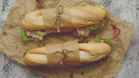 Sandwiches-with-ham-fresh-vegetables-and-herbs-served-on-brown-baking-paper-over-concrete-backdrop