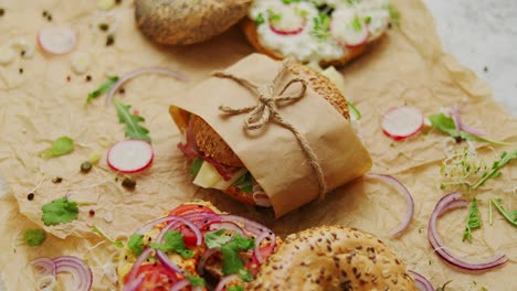 Bagels-with-ham-cream-cheese-hummus-radish-wrapped-in-brown-baking-paper-ready-for-take-away