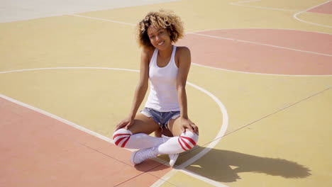 Attractive-young-woman-sitting-on-a-basketball