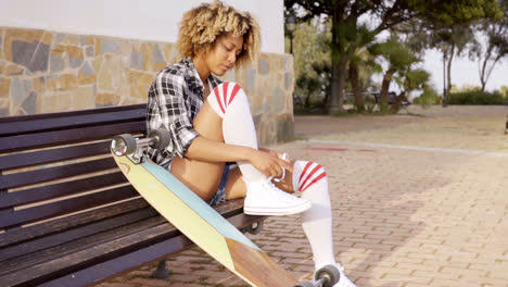 Young-woman-tying-shoes-with-skateboard-on-bench
