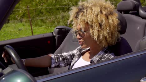 Trendy-young-woman-driving-a-sports-car