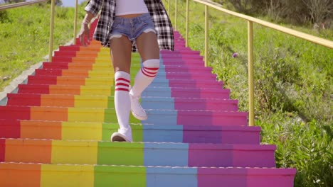Young-woman-descending-rainbow-colored-steps