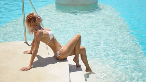Seductive-woman-in-white-swimwear-enjoying-sunlight-sitting-on-stone-steps-of-pool