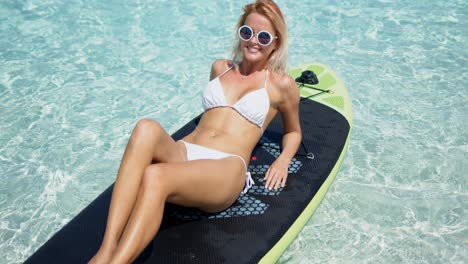 Happy-blonde-woman-sunbathing-on-paddle-board