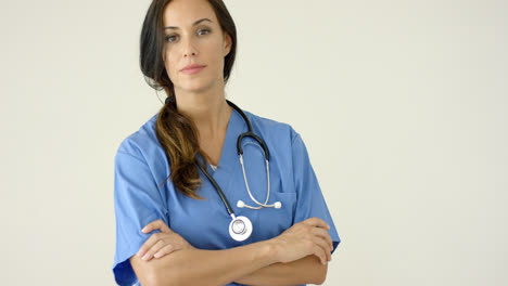 Woman-in-scrubs-crosses-arms-and-smiles-at-camera