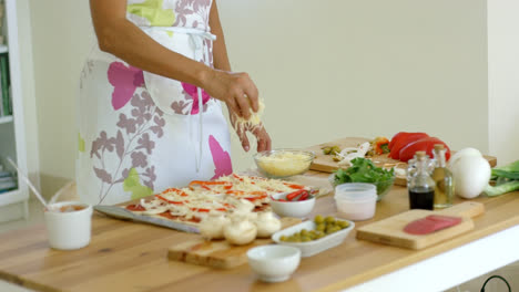 Woman-preparing-a-homemade-pizza-in-the-kitchen