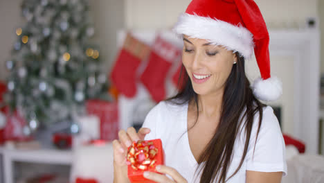Smiling-woman-unwrapping-her-Christmas-gift