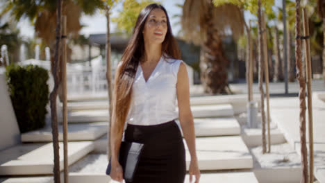 Young-businesswoman-walking-through-a-park