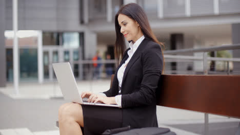 Business-woman-alone-with-laptop-on-bench